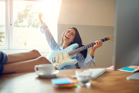 Laughing young woman holding hand up in celebration while playing a guitar and keeping her feet on table. Bright sunlight in window behind her