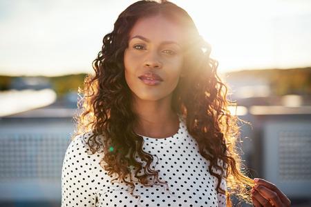 Jovem mulher sonhadora iluminado pelo sol nascente em pé em um telhado urbano brincando com seu lindo cabelo encaracolado longo como ela olha para a câmera