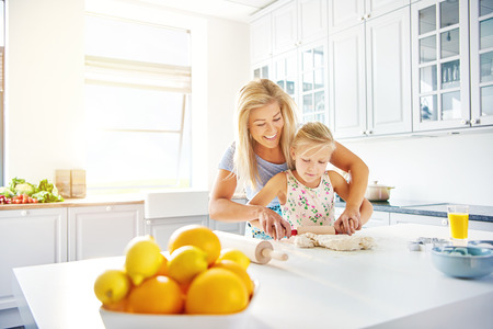 high key: Smiling happy young mother teaching her little daughter to bake in a high key bright white kitchen as they roll the dough together Stock Photo