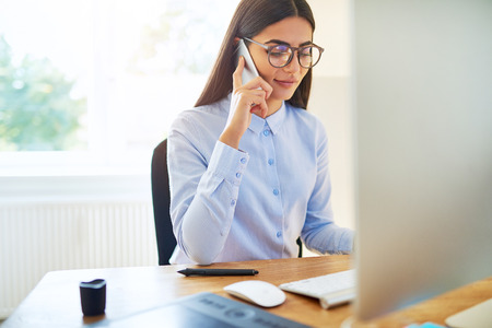 Young businesswoman in glasses talking on a mobile phone in the office as she sits at her desk working on a desktop monitor