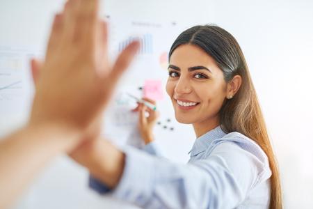事業展開についての概念のホワイト ボードの青いシャツ一体高 fiving 同僚の豪華なインドの女性 写真素材