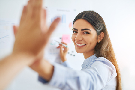 Gorgeous Indian woman in blue shirt high fiving coworkers at white board for concept about business development Stockfoto