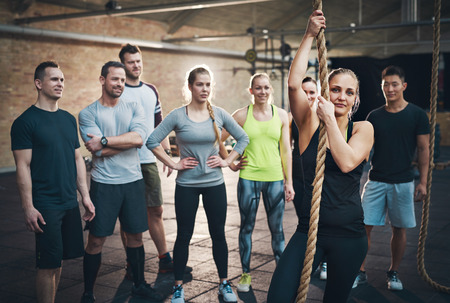regimen: Group of adults watching woman use climbing rope in fitness exercise circuit training regimen