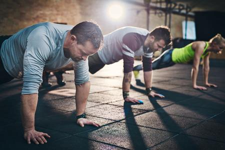 그들 위에 밝은 빛 플레어와 실내 체력 크로스 훈련 운동 시설에서 운동 훈련을 수행하는 성인 그룹