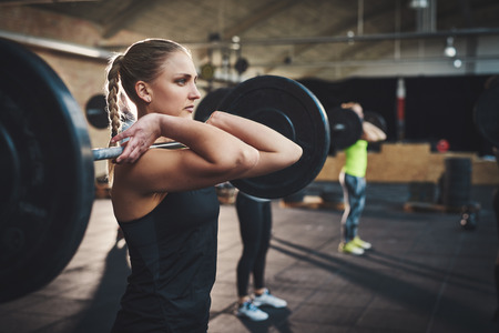 floor mats: Tough woman with thick muscular arms pulling up large barbell in fitness training class with other adults and black floor mats indoors