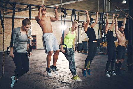 cross bar: Group of six young and strong male and female adults doing chin ups with bar and straps in cross fit training gym
