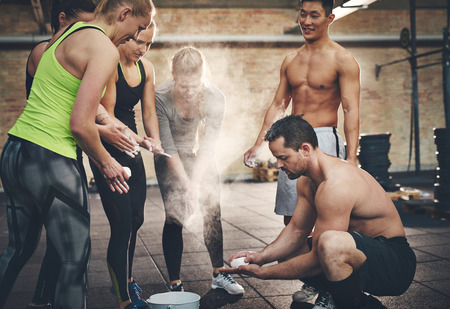 requiring: Athletic adults applying talcum powder to hands before doing intense workouts requiring a firm grip Stock Photo