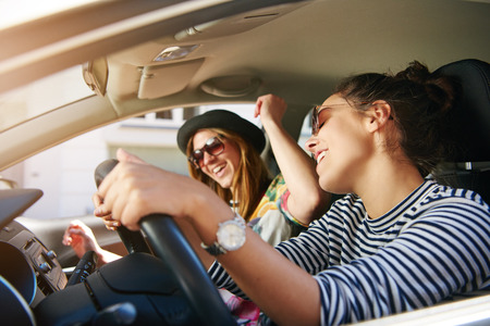 holiday music: Two trendy attractive young woman singing along to the music as they drive along in the car through town viewed through the open side window Stock Photo