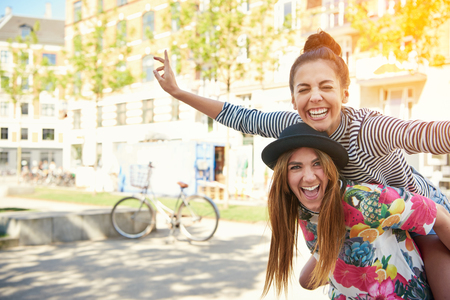 gaiety: Laughing young female friends piggy back riding outdoors on a residential urban street posing with outstretched arms like an airplane, with copy space and sun glow Stock Photo