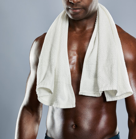 Identificeerbaar gespierde borst van de zwarte man met een handdoek om de schouders over grijze achtergrond met een kopie ruimte