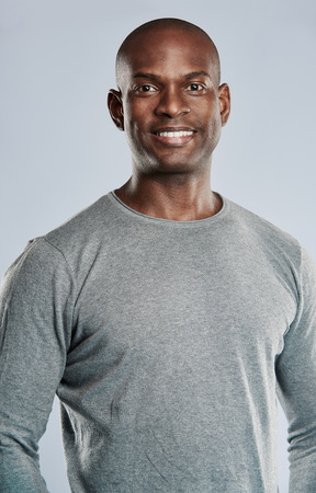 physique: Single handsome smiling Black man with shaved head in gray shirt with muscular physique over plain background Stock Photo
