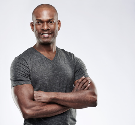 Single handsome grinning confident young Black adult with shaved head and folded muscular arms over gray background with copy space
