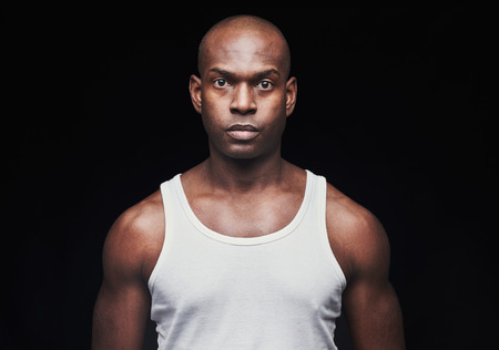 unemotional: Single serious young black man with shaved head and unemotional expression in white undershirt over dark background