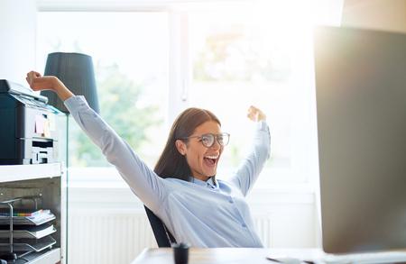 판매 종료 또는 좋은 소식 읽기를 축하하는 것처럼 팔을 확장 한 소규모 사무실의 즐거운 여인