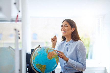 exultant: Laughing woman pointing to country on globe in bright classroom or office for concept about education and geography