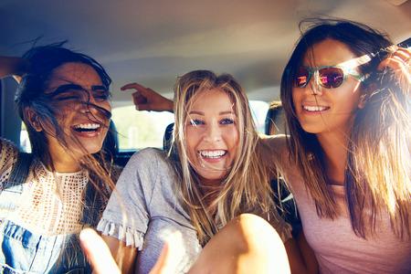 Drie mooie gelukkige meisjes in een auto reizen als passagiers op een road trip lachen en een grapje a ze glimlachen naar de camera