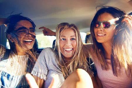 Three beautiful happy girls in a car travelling as passengers on a road trip laughing and joking a they smile at the camera Stock Photo