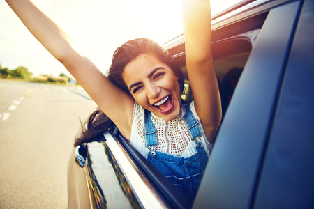 exuberant: Cheering laughing young teenage girl hanging out of an open car window as it drives along a rural road with her arms extended in the bright early morning sun