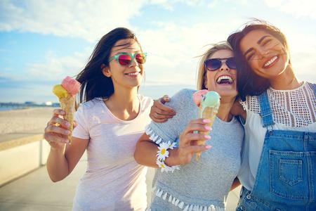 Lachende tiener meisjes eten van ijs kegels als ze lopen langs een boulevard arm in arm genieten van hun zomervakantie