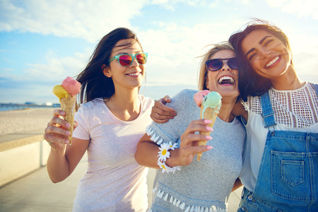 three women: Laughing teenage girls eating ice cream cones as they walk along a beachfront promenade arm in arm enjoying their summer vacation