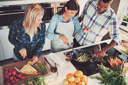 トマト、チーズ、アスパラガス、フルーツ、キッチン カウンター、ストーブに他の原料が付いている食事を調理のトリオのハイアングル