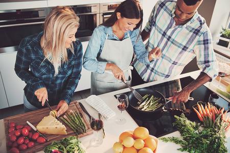 High Angle oog van trio het koken van een maaltijd met tomaten, kaas, asperges, fruit en andere ingrediënten op aanrecht en fornuis