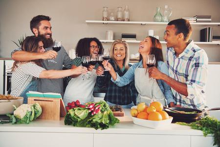 室内で大きなキッチン カウンターを食べる何かを調理しながらワイングラスを焼く楽しいグループ 写真素材
