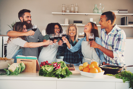 Fun group toasting wine glasses while cooking something to eat at large kitchen counter indoors