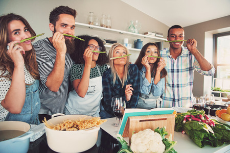 best group: Group of six diverse silly adults sniffing asparagus stalks in kitchen. Bowl of pasta and vegetables are on the table.
