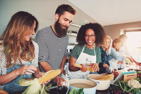 Feliz grupo de hombres y mujeres adultos jóvenes cocinar juntos en casa en una pequeña cocina o en el aula culinaria