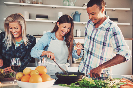 Tre giovani amici adulti friggere il cibo in padella insieme. Ingredienti per il pasto sono di fronte a loro. Archivio Fotografico - 63754568
