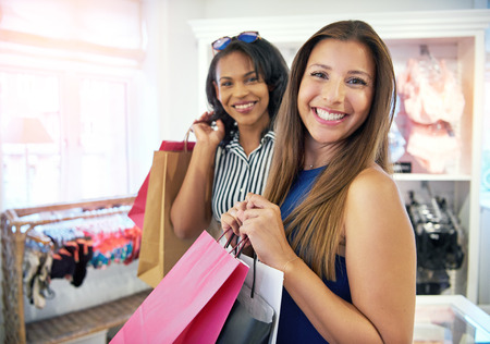 Two happy female friends shopping together in a clothing store holding their purchases in colorful bags as they stand smiling at the camera