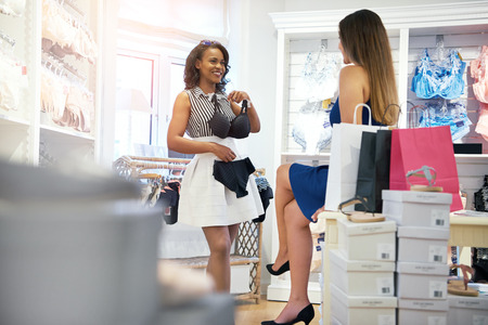 boutique: Two young woman choosing lingerie in a fashion store standing holding up a black bra and panties with a smile for an opinion from her friend
