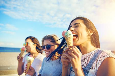 彼らは彼らの休暇の間に夏の暑い日にウォーター フロントの遊歩道に沿って散歩を食べる 3 つの若い女氷の海辺でクリーム コーン