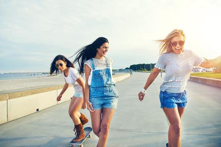 그들이 해변 산책로를 따라 스케이트 보드로 웃고있는 해변에서 이른 아침을 즐기고있는 평온한 젊은 매력적인 여성들의 트리오