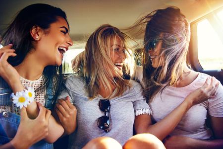 Drei lebhafte junge Frauen in der Rückseite eines Autos lachen und scherzen, wie die Winde weht ihre langen Haare über ihre Gesichter, wie sie reisen Standard-Bild - 63910755