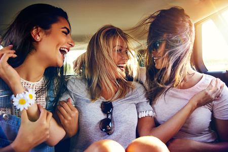 Three vivacious young women in the back of a car laughing and joking as the winds blows their long hair over their faces as they travel Stock Photo
