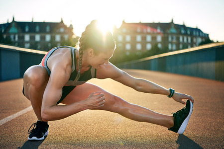 Female jogger stretches one muscular leg while placing all her weight on the other Stock Photo
