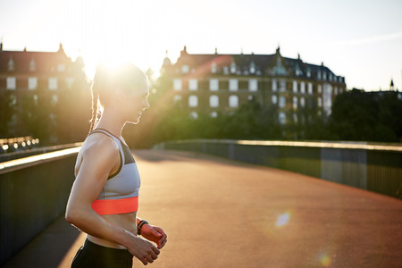 athletic wear: Woman in athletic wear exercising outdoors on an empty road by apartment houses