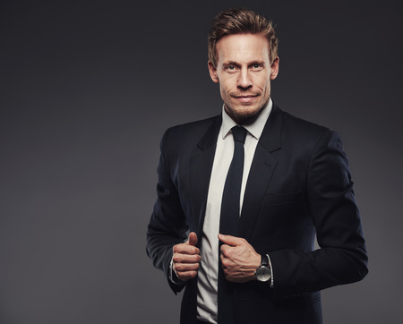 lapels: Handsome young businessman in a black suit holding his jacket lapels, standing against a gray background