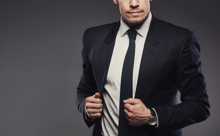 lapels: Closeup of midsection of a young businessman in a black suit holding his jacket lapels, standing against a gray background Stock Photo