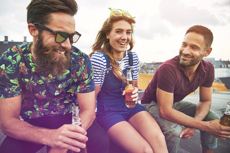 inebriated: Three attractive and young adult friends drinking from open beer bottles together on roof in urban setting during summer