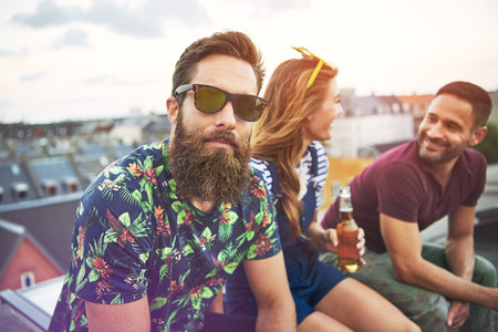 camaraderie: Handsome bearded man in colorful shirt and sunglasses sitting with friends on roof