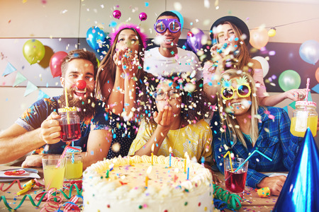 Group of six male and female festive partygoers in front of large white frosting covered cake surrounded by confetti in room Stockfoto
