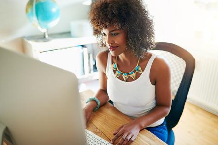漂亮的年輕女子從家裡的明亮通風辦公室開始營業,在桌面顯示器上閱讀信息