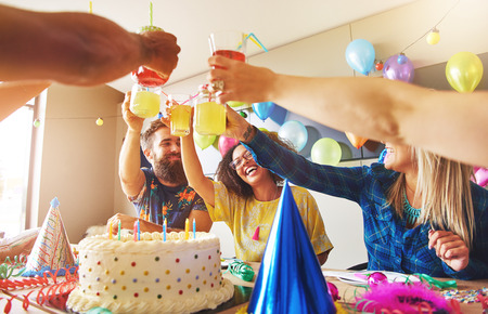hilarity: Group of young adult friends or coworkers toasting with yellow drinks over birthday cake Stock Photo