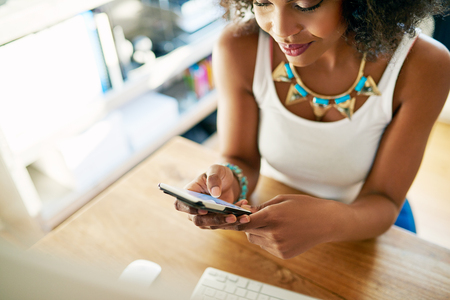 Stylish young businesswoman checking her mobile phone for text messages as she sits at her desk in an office, close up high angle cropped view Stock Photo