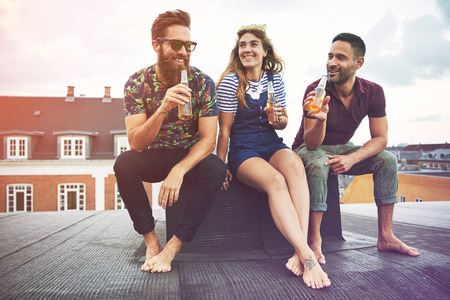 merrymaking: Happy group of three barefoot adults drinking beer on roof outdoors with copy space in sky