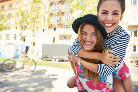 Pair of cute female friends in striped and flowery shirts holding each other outside as if to pose for a photograph. Includes copy space.