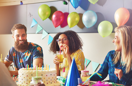 merrymaking: Smiling beautiful young woman sipping from yellow drink near birthday cake at party. Male and female friends sitting at left and right.